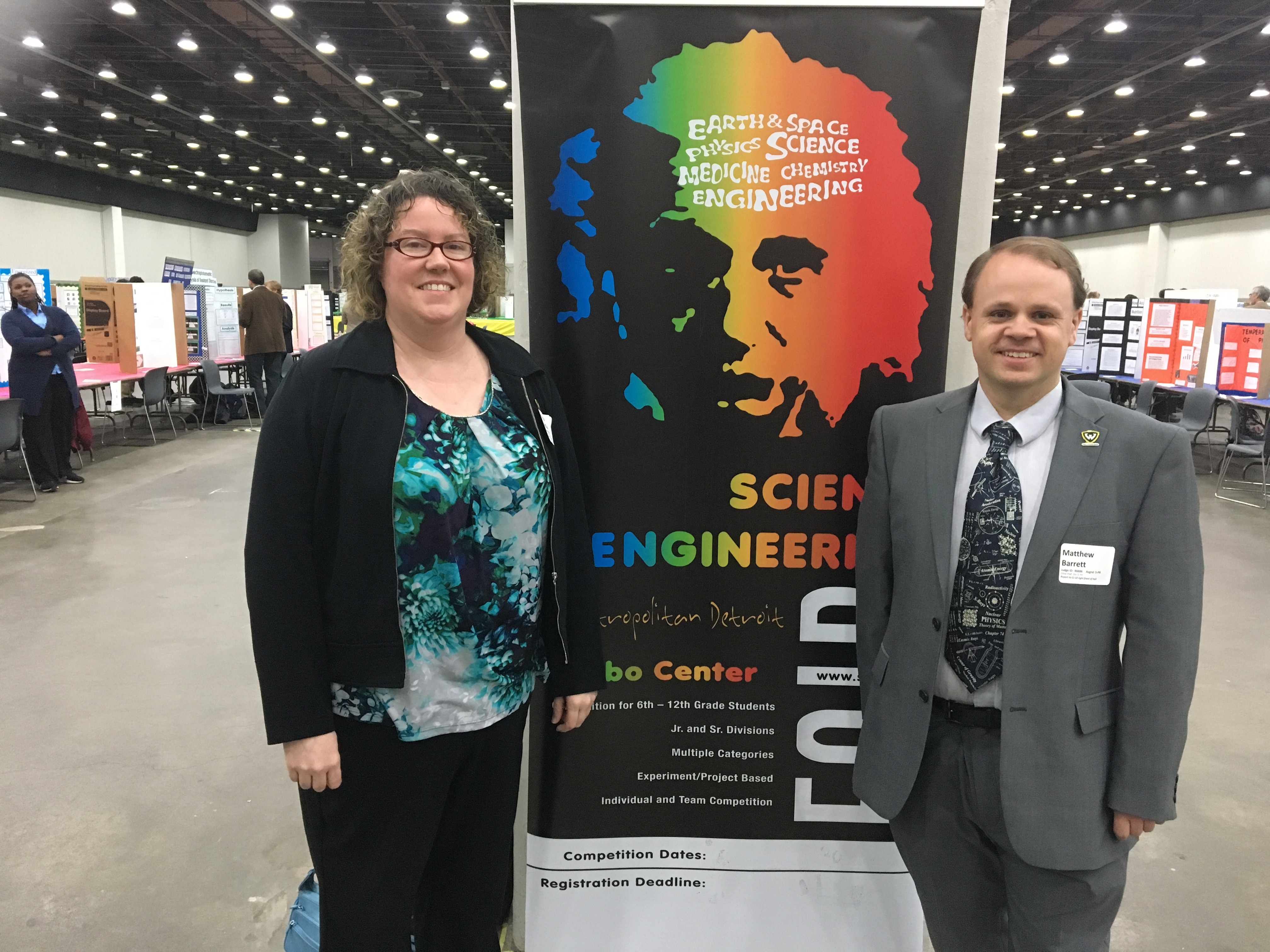Megan McCullen and Matthew Barrett stand with the banner for the Science Fair, a rainbow colored image of Albert Einstein